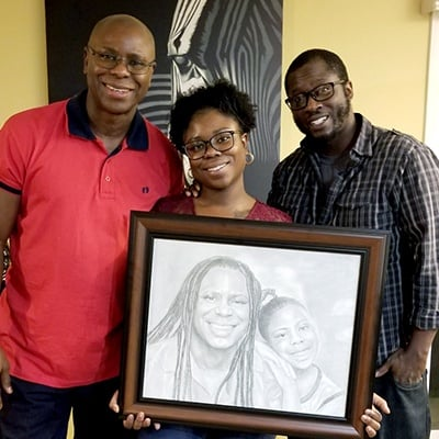 Family holding a drawn portrait